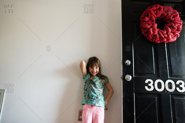 Little girl standing by an open front door