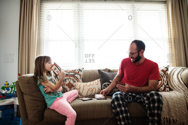 Father and daughter playing card game on a sofa