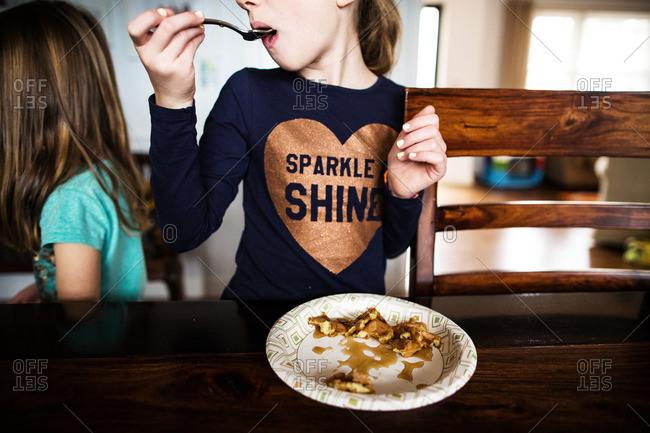 Little girl eating waffles for breakfast