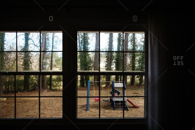 View of backyard swing set through window