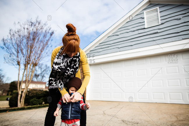 Mother zipping up toddler's vest in their driveway