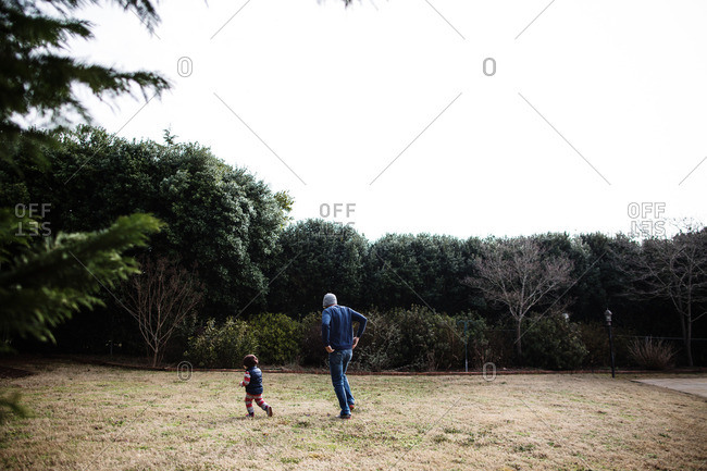Father chasing little boy around yard