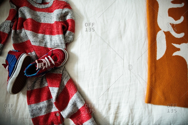 Red and gray striped outfit for toddler on a bed