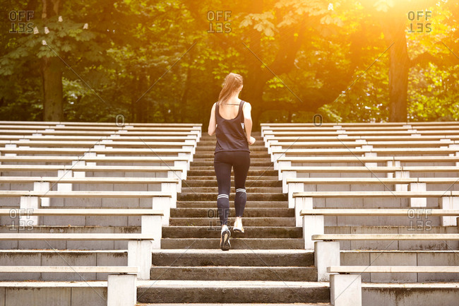 Rear view of young woman training, running up stadium stairway