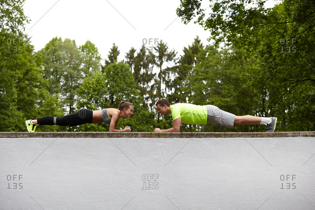 Young man and woman training, doing push ups opposite each other on top of wall