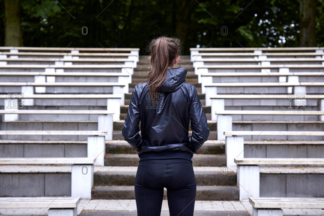 Rear view of young woman training, preparing to run up stadium stairway