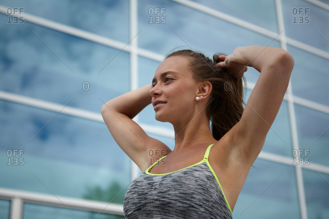 Young woman training, tying ponytail in front of office building