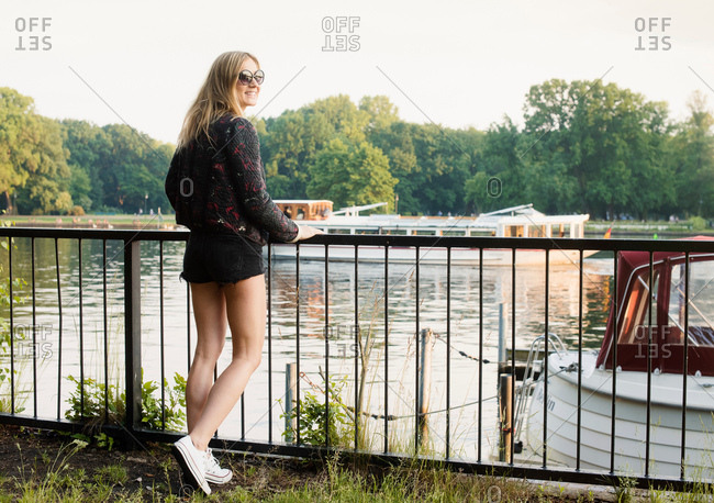 Young leaning on railings at waterfront, looking over shoulder