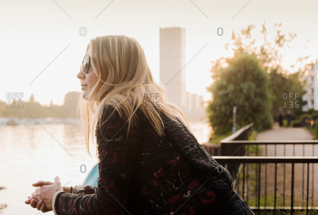 Young leaning on railings at waterfront, looking at view