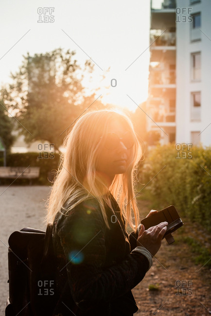 Young woman outdoors, at sunset, using smartphone