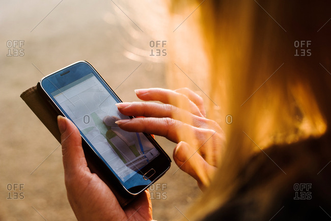 Young woman outdoors, using smartphone, close-up