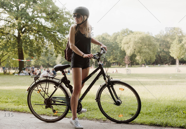 Young woman in park, preparing to ride bicycle
