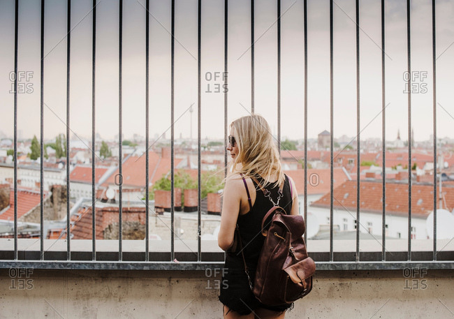 Young woman looking through railings, at view across rooftops, rear view