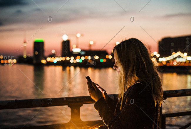 Young woman by waterfront, at dusk, using smartphone