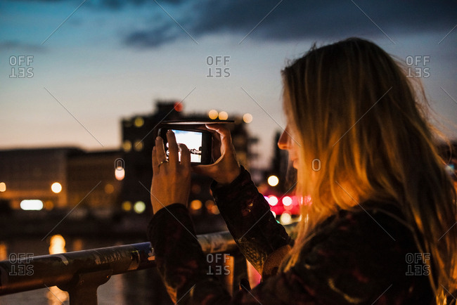 Young woman by waterfront, at dusk, photographing view with smartphone
