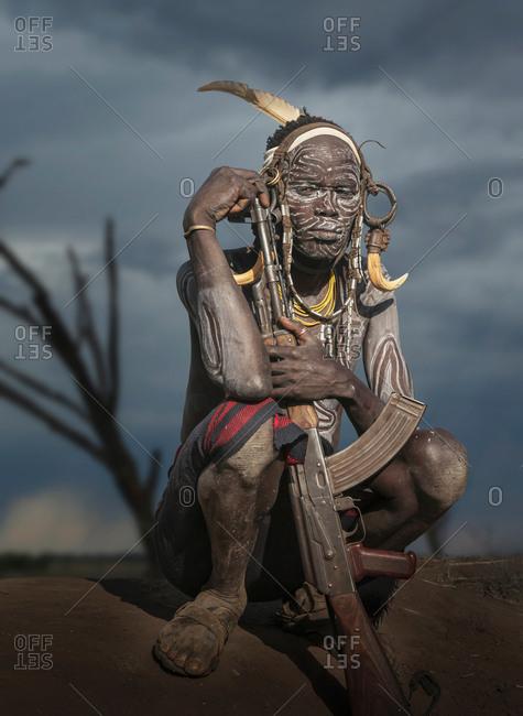 Young warrior of the Mursi tribe with Kalashnikov gun, Omo Valley, Ethiopia