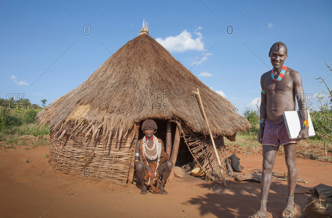 Man of the Karo tribe with laptop, while his wife in a hut is watching, Omo Valley, Ethiopia