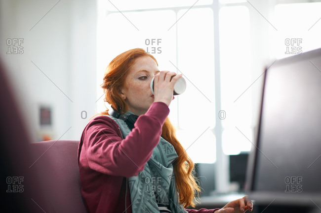 Young female college student at computer desk drinking takeaway coffee