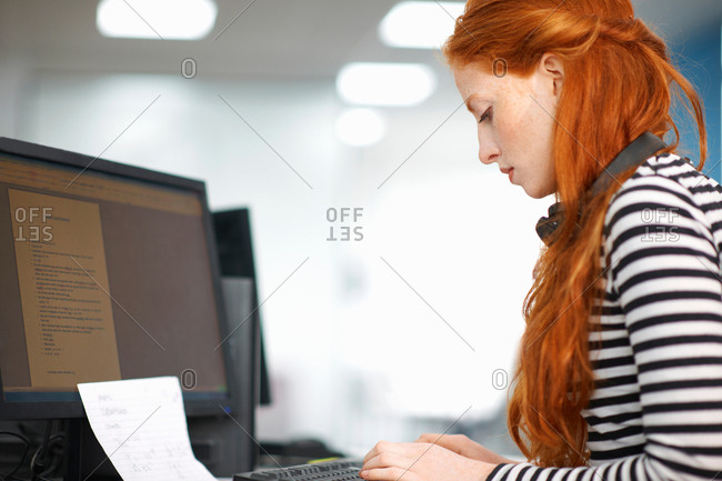 Young female college student typing at computer desk
