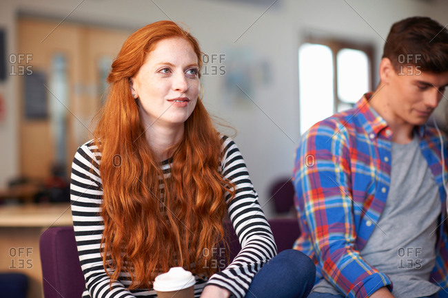 Young female college student sitting with takeaway coffee in common room
