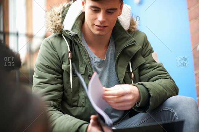 Young male college student revising on campus