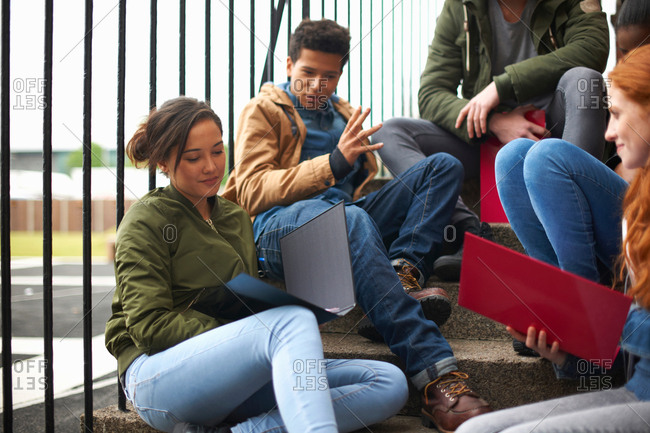 Young adult college student friends revising on campus stairs