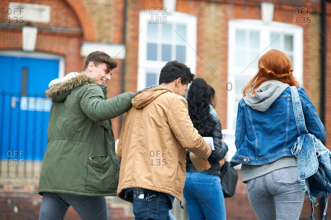 Male college student patting friends back on campus