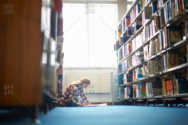 Young female college student working on library floor
