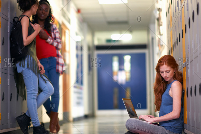 Young female college student sitting on locker room floor reading whilst typing on laptop