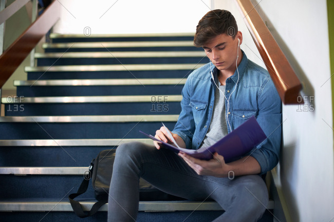 Young male college student sitting on stairway revising from file