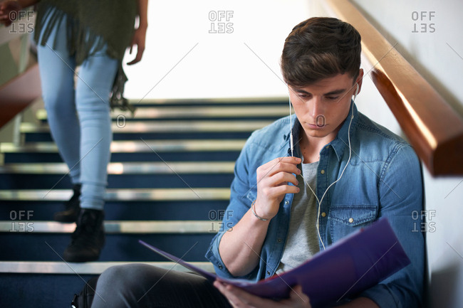 Young male college student sitting on stairway reading file