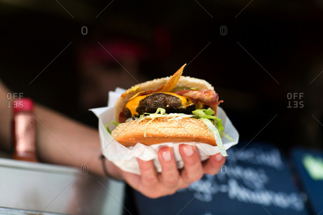 Man\'s hand serving hamburger from fast food van