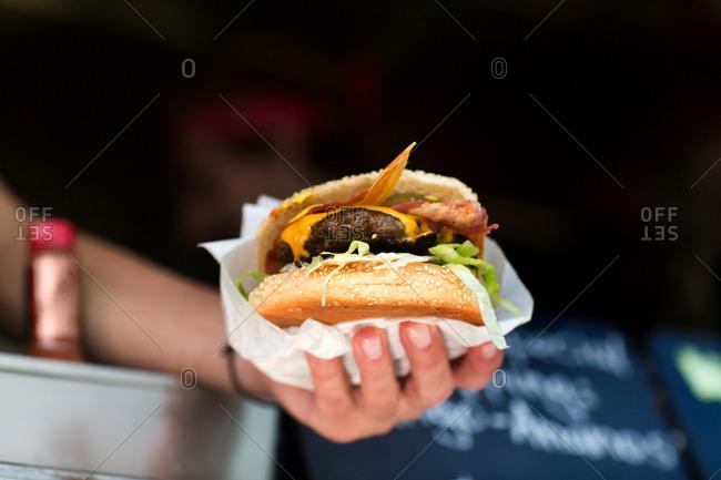 Man's hand serving hamburger from fast food van