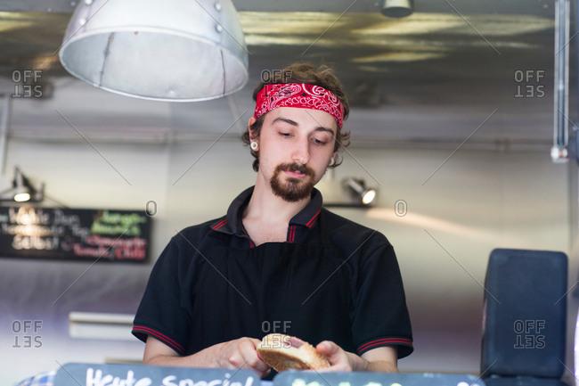Young man slicing hamburger bread roll on fast food van
