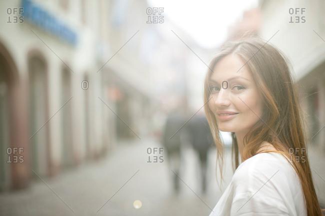 Portrait of beautiful woman on city street, Freiburg, Germany