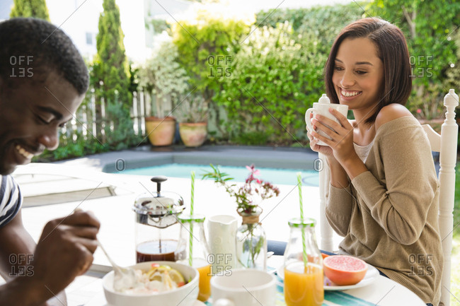 Young couple sharing eating breakfast together by swimming pool