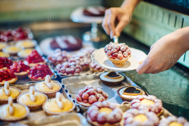 Woman's hands selecting fruit tart in cake shop, Florence, Italy