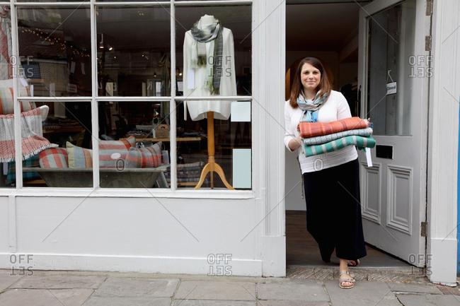 Shop owner in doorway holding fabric