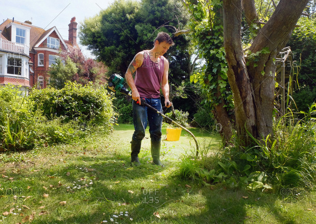 Mature man, gardening, using strimmer