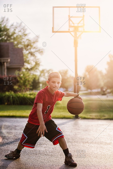 Portrait of young boy dribbling with basketball