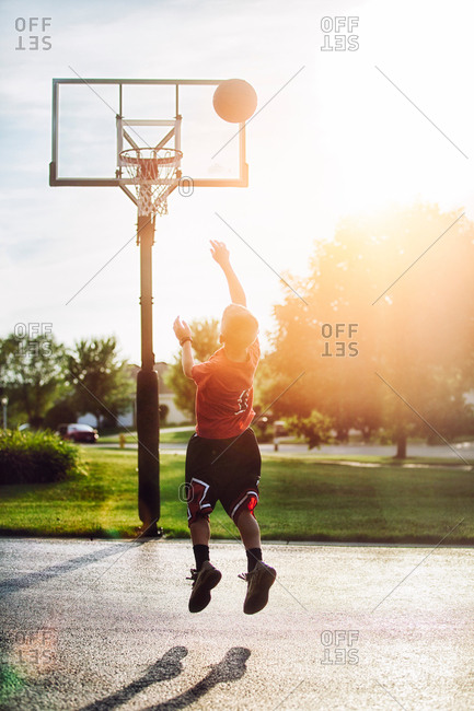 Young boy shooting basketball jump shot