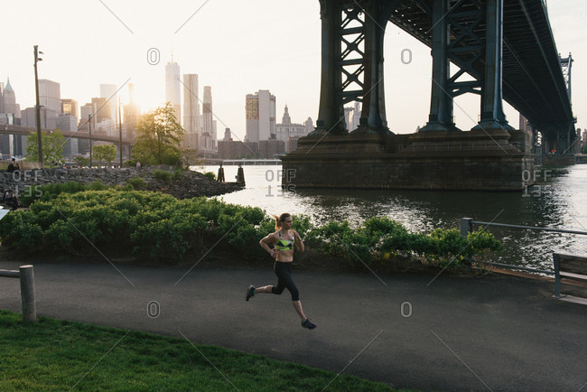 Young woman exercising outdoors, running along pathway underneath Brooklyn Bridge, Brooklyn, New York, USA