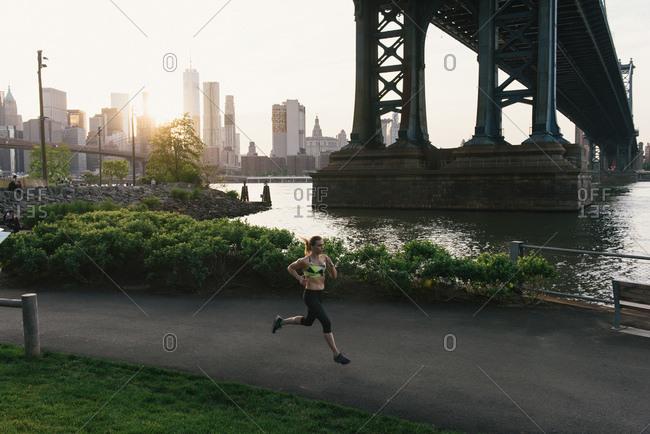 Young woman exercising outdoors, running along pathway underneath Brooklyn Bridge, Brooklyn, New York, USA