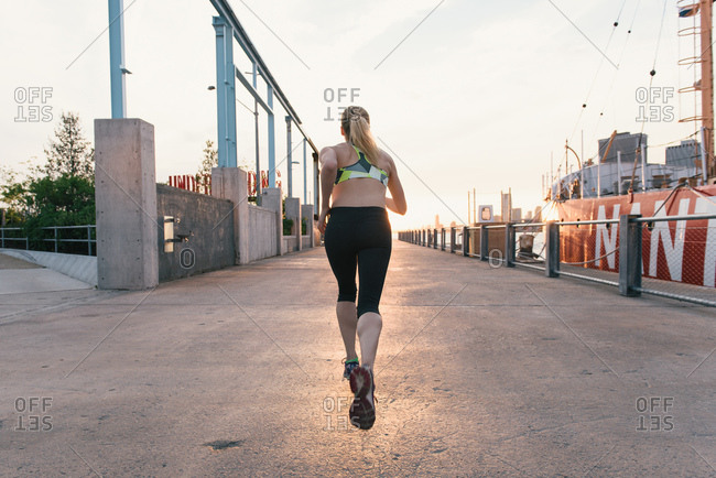 Young woman exercising outdoors, running along waterfront, rear view, Brooklyn, New York, USA