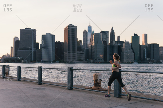 Young woman exercising outdoors, running along waterfront, Brooklyn, New York, USA
