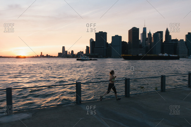 Young woman exercising outdoors, running by waterfront, Brooklyn, New York, USA