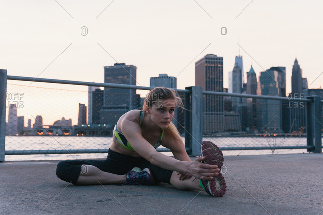 Young woman exercising outdoors, stretching by waterfront, Brooklyn, New York, USA