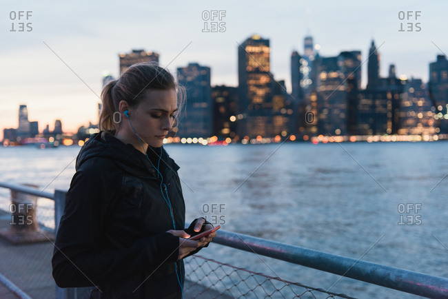 Young woman by waterfront, using smartphone, Brooklyn, New York, USA
