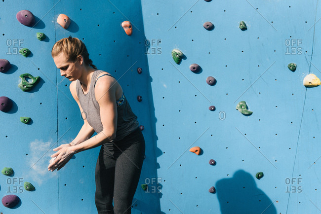 Young woman dusting hands, preparing to use climbing wall, Brooklyn Bridge Park, Brooklyn, New York, USA