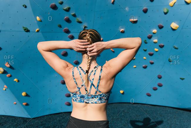 Young woman securing hair, preparing to use climbing wall, rear view, Brooklyn Bridge Park, Brooklyn, New York, USA